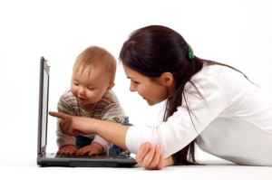 adult showing baby how to use computer