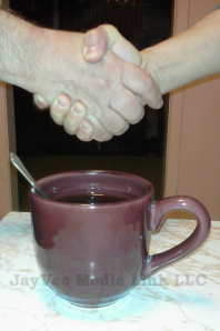handshake over coffee cup